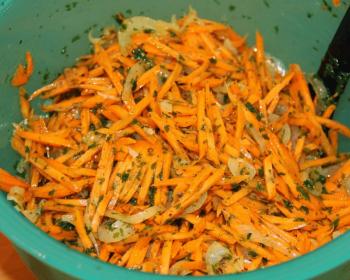 салат морковча, в котором морковь нарезанная соломкой, с жаренным луком, зеленью и подсолнечным маслом в зеленой миске с черной ложкой