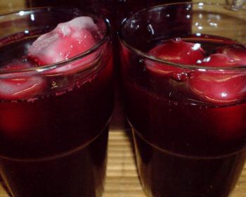 два стакана с морсом из черной смородины с кубиками льда на столе