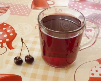 вишневый морс в прозрачной кружке и вишенки на столе, застеленном клетчатой скатертью с узором