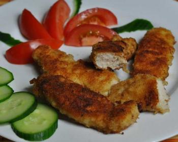 куриные наггетсы в панировке с нарезанными помидорами и огурцами на тарелке