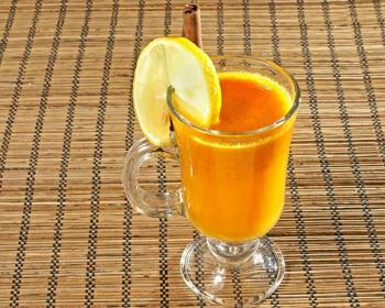 облепиховый сбитень с долькой лимона в стеклянной чашке на столе, застеленном деревянным ковриком