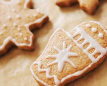 новогоднее печенье в форме снежинок и рукавичек, украшенное белой глазурью