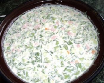 темная глубокая тарелка с окрошкой на айране со свежей зеленью