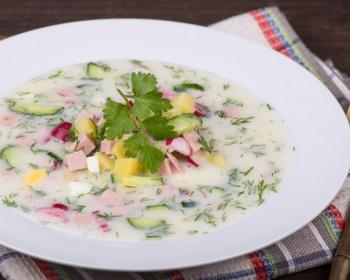 окрошка на сметане и воде с кусочками картошки, редиски, колбасы и укропа, украшенный листиками петрушки, в белой тарелке на столе, рядом ложка