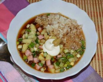 зимняя окрошка с черной редькой, картошкой и вареной колбасой на квасе в тарелке на столе