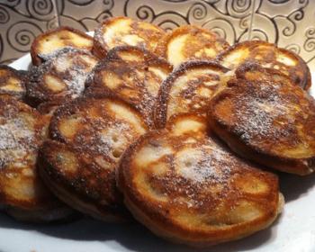 пышные оладьи с творогом, присыпанные сахарной пудрой, на белой круглой тарелке