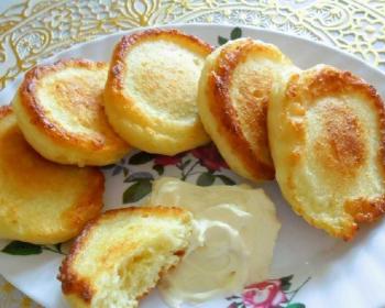 пять золотистых оладьев и половинка оладушка, приготовленных на кефире, рядом сметана на тарелке с розовыми цветами, на золотистой скатерти, на столе