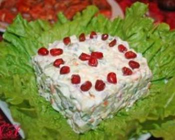 на тарелке, укрытой свежими листьями салат, лежит порция салата оливье по-царски, сверху на салате лежат зерна граната