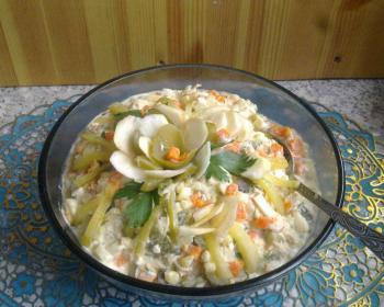 в большой прозрачной пиале лежит оливье с курицей и яблоками, в салате лежит столовая ложка, вверху на салате цветок из яблочных слайсов