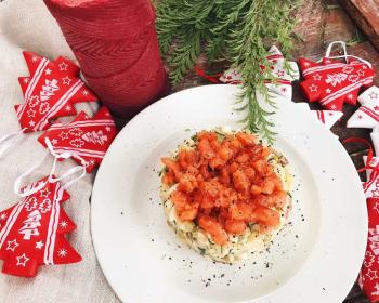 на белой круглой тарелке лежит салат оливье с рыбой, нарезанной небольшими кубиками, возле тарелки лежат декоративные елочки