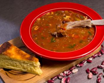 солянка с фасолью, орехами, мясом и зеленью в тарелке