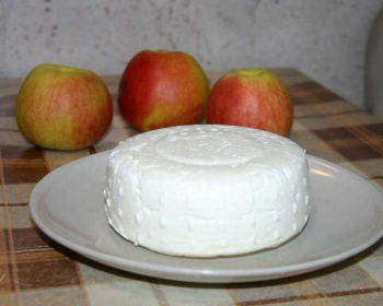 головка осетинского сыра в тарелке на столе, на фоне три яблока