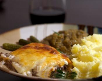 кусочек отбивной из говядины, покрытый расплавленным сыром, картофельное пюре и соленые огурчики на тарелке
