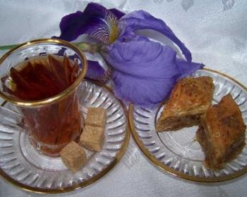 пахлава из теста фило на стеклянном блюдце с золотой каемочкой, рядом стеклянная чашка с чаем на стеклянном блюдце, рядом лежат три кусочка коричневого сахара, на фоне фиолетовый цветок ирис