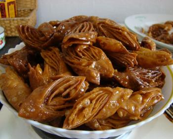 жареная пахлава, политая сиропом, сложенная в глубокую белую тарелку на столе