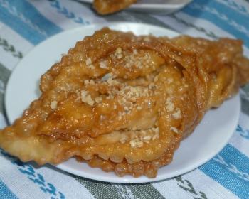 медовая пахлава, политая сиропом и посыпанная, на белой тарелке на столе, застеленном скатертью
