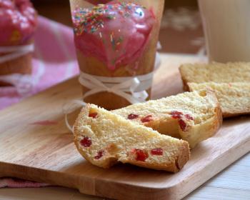 панеттоне с цукатами, разрезанный на четвертинки, на деревянной доске, рядом целый пасхальный кекс