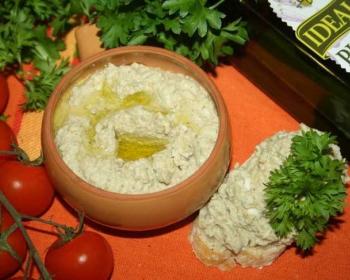 паштет из баклажанов в глиняном горшочке, зелень, помидоры и бутолка оливкового масла на столе