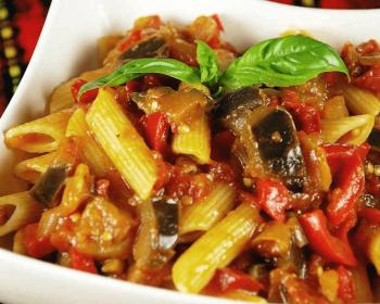 овощная паста с баклажанами в белой квадратной тарелке, украшенная свежими листочками базилика