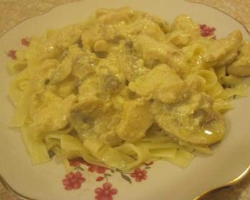 паста с курицей и грибами в сливочном соусе в тарелке с золотой каемочкой