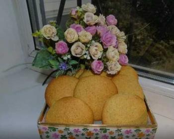 круглое печенье из кукурузной муки в квадратной коробке на подоконнике, сверху лежит букет цветов