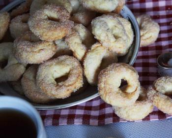 печенье на пиве с сахаром в глубокой тарелке, ложка и кружка с чаем на столе, застеленном клетчатой тканевой салфеткой,