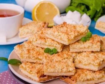 печенье Венское с вареньем, сложенное горкой на тарелке и украшенное листочками свежей мяты, на фоне чашка с чаем
