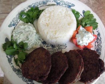печеночные котлеты с рисом на тарелке с зеленью и овощами на столе