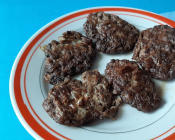 пять оладий из говяжьей печени в тарелке на столе