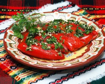 на красивом полотенце с орнаментом стоит тарелка с узорами, на ней лежат перцы, фаршированные сыром, сверху присыпанные измельченным чесноком и зеленью, рядом лежит веточка петрушки и укропа