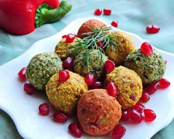 не белой тарелке квадратной формы лежат пхали в виде шариков из фасоли, сверху лежит веточка укропа, блюдо присыпано зернами граната, рядом на столе лежит половинка красного болгарского перца