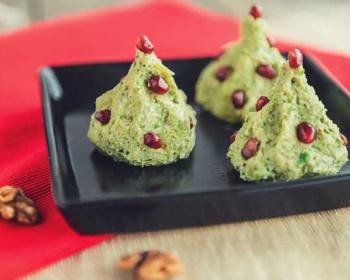 зеленые пхали из капусты, украшенные зернами граната, на черной квадратной тарелке на столе, рядом кусочки грецкого ореха