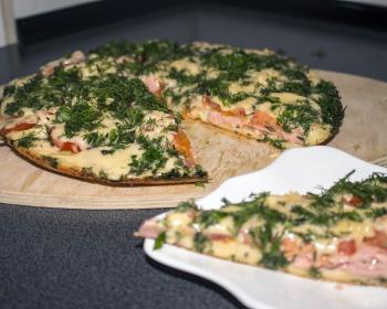 разрезанная пицца, приготовленная на сковороде