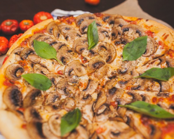 пицца с шампиньонами, сыром и зеленью на столе