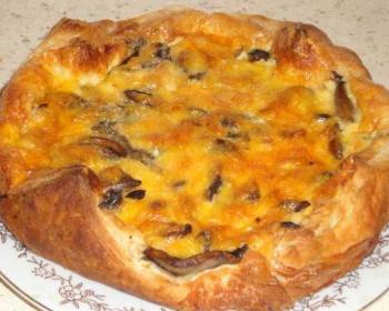 открытый пирог из слоеного теста с курицей и грибами в тарелке на столе