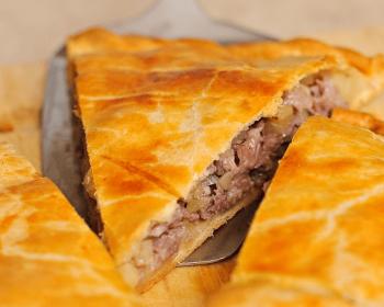 пирог мясной с картошкой, разрезанный на треугольные кусочки