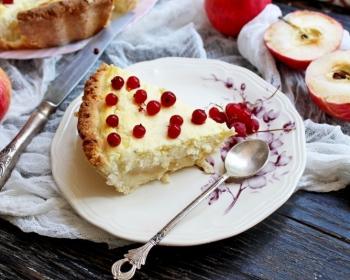 треугольный кусочек пирога с творогом и яблоками, украшенный ягодами красной смородины, на блюдце, рядом чайная ложечка, на фоне яблоки, марля, столовый нож, остаток пирога