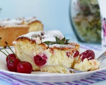 кусочек пирога с творогом и вишней, присыпанный сахарной пудрой, на белой плоской тарелке с ложкой на столе, застеленном скатертью