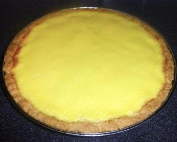 круглый пирог сметанник в блюде на столе