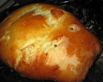 на столе лежит пирог в форме свинки с рисом и свиным фаршем, запеченный до золотистого цвета
