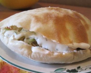 запеченная пита с кусочками мяса и салатом внутри на белой тарелке на столе