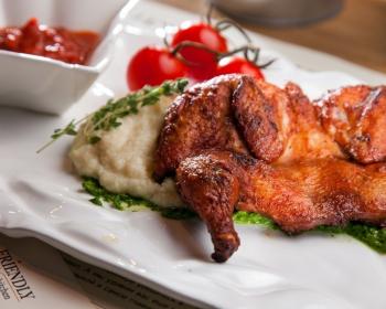 пюре из корня сельдерея, украшенное веточками тимьяна, с запеченной курицей и зеленым соусом на белой плоской тарелке на столе