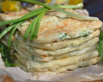 плацинды с творогом и зеленью, сложенные стопкой, украшенные зеленым луком, на тарелке