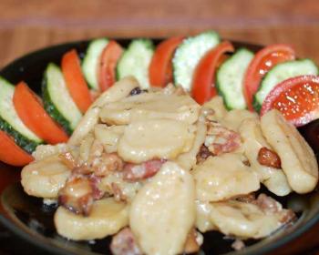 полтавские галушки со шкварками на тарелке, по краю тарелки выложены помидор и огурец дольками