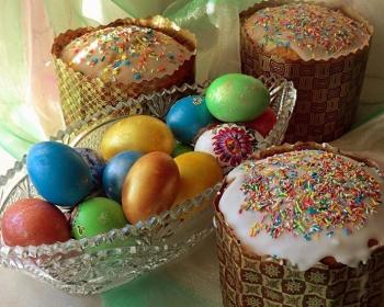 помадка на пасхальных куличах, рядом вазочка с крашенными яйцами на столе