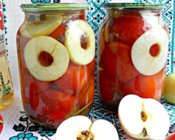 помидоры с яблоками, нарезанными кольцами, в банках на зиму стоят на столе, рядом бутылка с уксусом, яблоки (целое и разрезанное пополам) и свежие помидоры