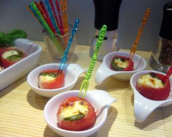 помидоры, запеченный с сыром, в тарелочках со шпажками на столе, стакан с цветными палочками и баночка с перцем на фоне