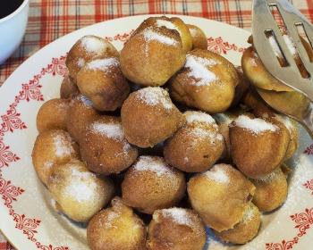 жареные пончики со сгущенкой, присыпанные сахарной пудрой, на плоской тарелке на столе, застеленном скатертью