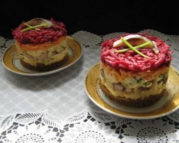 на двух блюдцах с золотой каёмочкой лежат два порционных салата селедка под шубой на хлебе, сверху лежит маленький кусочек сельди и перья зеленого лука