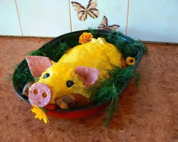 в овальной емкости для запекания лежит фальшивый поросенок из картофеля, пятачок и ушки сделаны из колбасы, ножки из сосисок, вокргу готового блюда лежит свежая зелень укропа и цветы